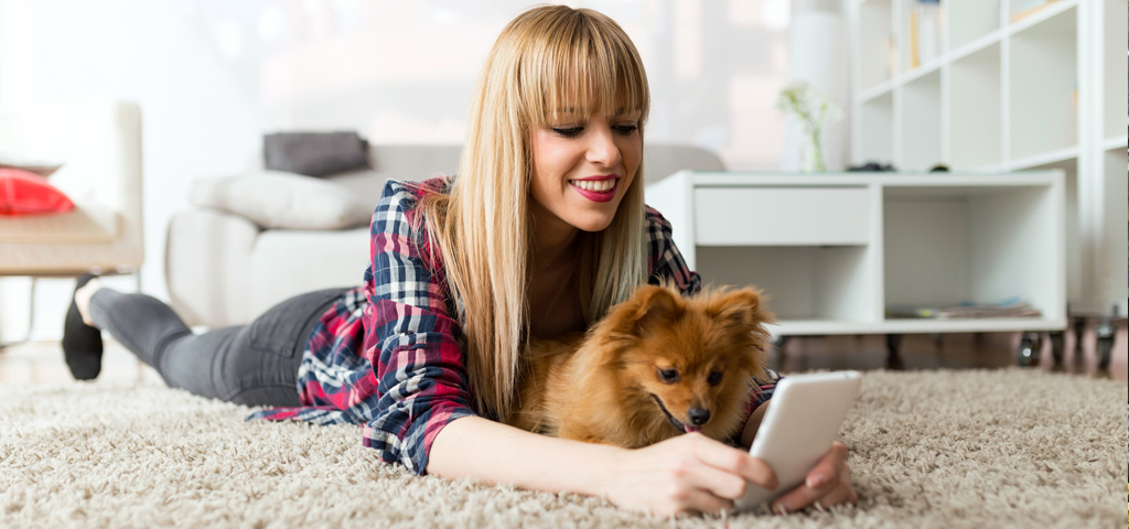 A young woman and her Pomeranian looking at a mobile phone screen