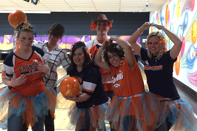 People smiling while dressed in Bronco's attire while bowling.