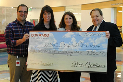 4 people smiling and holding a check for $8,850.05 that is being donated to the Children's Hospital of Colorado.