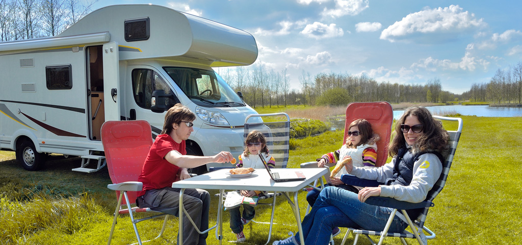 family of 4 outside eating, next to RV