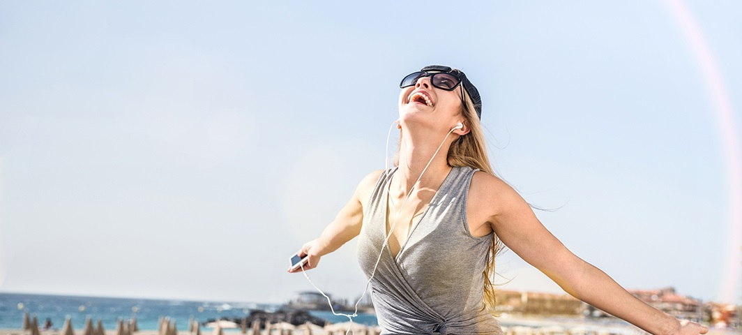 happy woman at beach with headphones