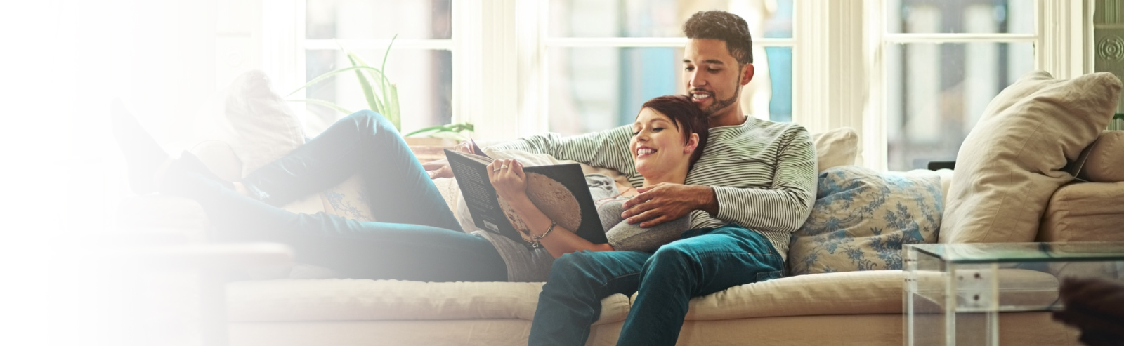 Man and woman couple laying on couch reading a book together.