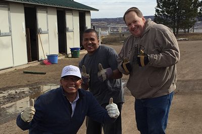 3 men smiling while wearing work gloves outside.