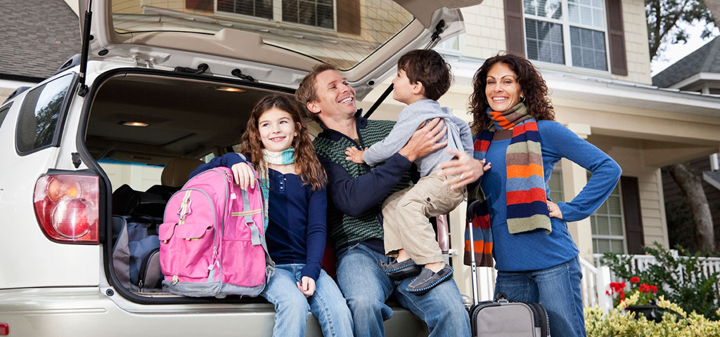 A happy family posing next to the back of their car